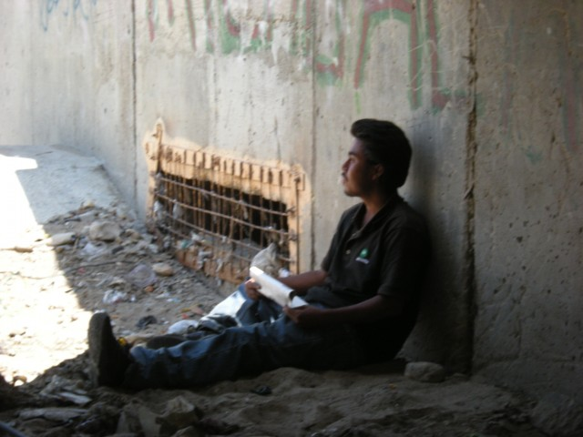 Migrant waits in a culvert for the opportunity to cross.