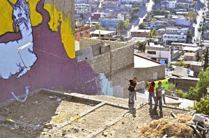 Boys fly kites in the empty lot below Once's piece in the Tijuana colonia Camino Verde.